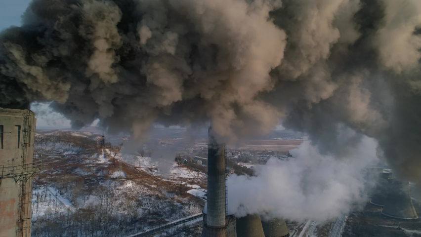 Drone around toxic enterprise chimneys tubing against the sky background release black smoke. Factory pollutes environment. Russia Primorsky Krai industrial countryside landscape. Winter day. Aerial