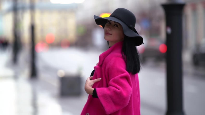 Portrait of a pretty black-haired woman in a pink coat and black hat walking on a blurry background of a city street near the road. Smiling and posing. | Shutterstock HD Video #1062023335