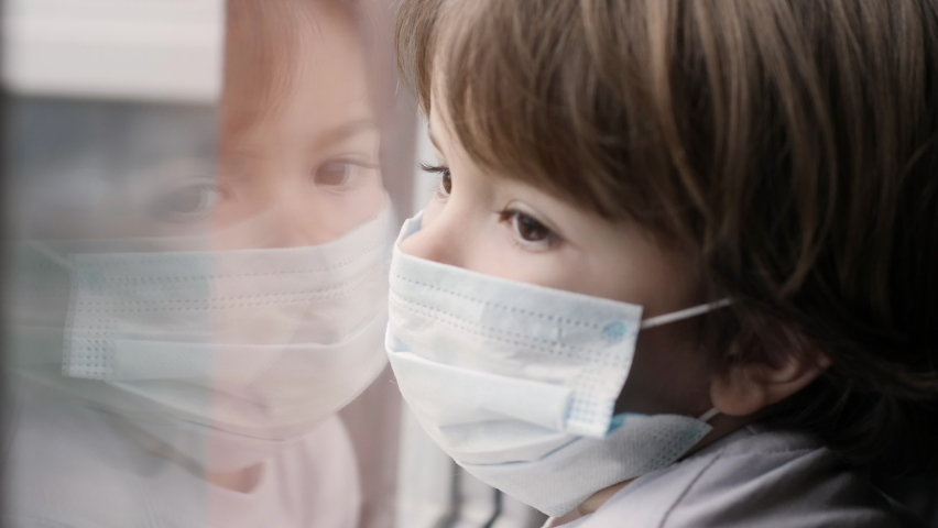 Little Child Boy With Protective Mask, Sad Looking Through Window Worried About Covid-19 Lockdown. Kid In Protection Mask Looking Out Window Home. Quarantine Coronavirus Social Distancing Royalty-Free Stock Footage #1062024472