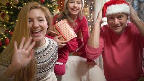 A happy couple with a child is celebrating Christmas with their friends using a video call. Family greeting their relatives on Christmas eve online. Social distancing, self isolation during quarantine