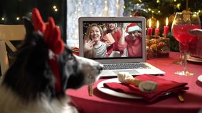 A couple with a child and mature man with a dog celebrating Christmas using a video call. People greeting their relatives friends on Christmas eve online. Social distancing, self isolation quarantine