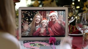 Two happy families with a children celebrating Christmas using a video call. Family greeting their relatives and friends on Christmas eve online. Social distancing, self isolation during quarantine
