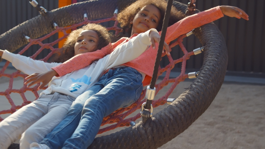 Smiling little african girls riding on swing with net outdoors. Portrait of adorable afro-american toddler sister lying on net swing and playing in park playground Royalty-Free Stock Footage #1062029458