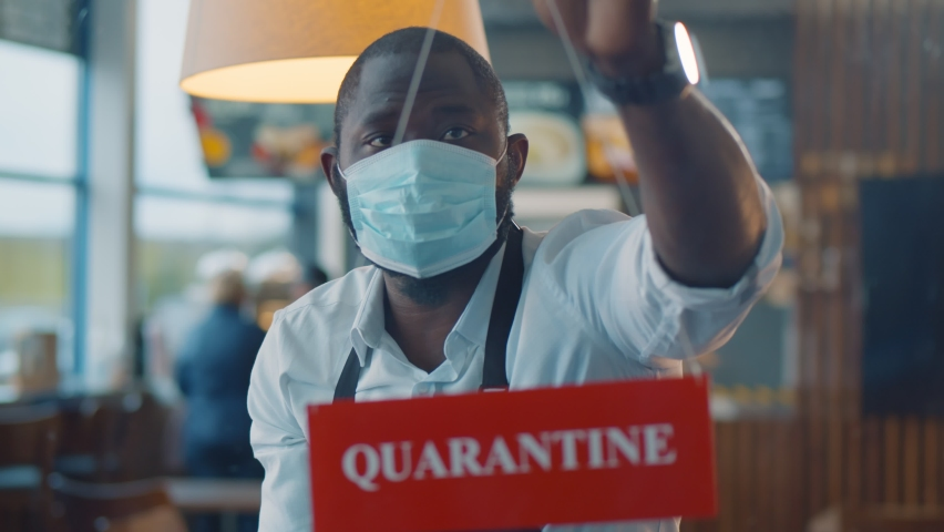 Afro-american waiter wearing safety mask hanging quarantine sign in glass door of cafe. Fast food restaurant owner putting quarantine sign on window shutting down because of coronavirus pandemic Royalty-Free Stock Footage #1062029563