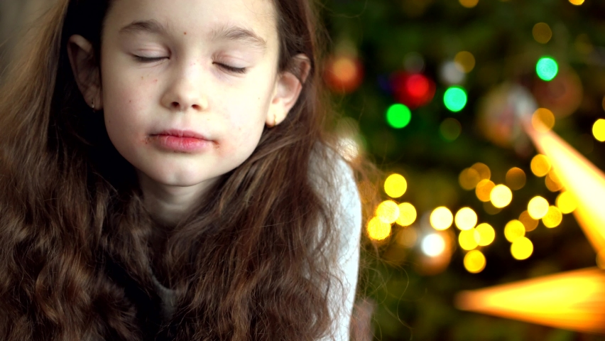 Portrait of happy little girl sitting near Christmas tree on new year's eve in decorated room. New Year and holidays with kids concept. Enjoying festive holiday celebration. 4k video | Shutterstock HD Video #1062029740