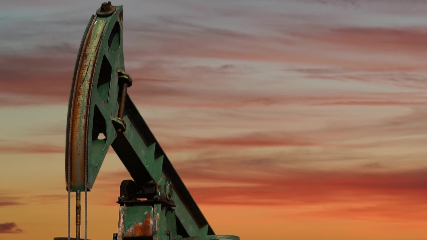Crude Oil Extraction at Sunset. Pump Jack Extracting Petroleum from a Oil Well. Fossil Fuel Energy. Oil Industry Equipment.