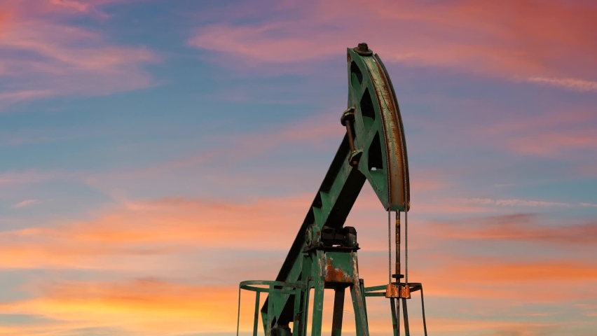 Pumping Oil Rig At Sunset. Pump Jack Extracting Crude Oil from a Oil Well. Fossil Fuel Energy. Oil Industry Equipment.
