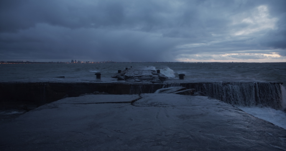 Storm waves crashing to the pier rocks and dark clouds in sky slow motion