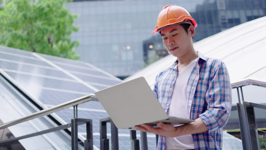 Engineer or construction worker Asian man is using  laptop to check solar cell replacement power system. Solar cell technology for building Or industrial factory. Hard hat help protect with operation Royalty-Free Stock Footage #1062042790