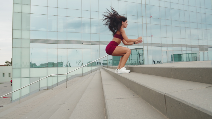 Workout cardio running up and jumping the stairs training. woman going run up steps. Latin Runner athlete doing cardio sport workout. Activewear leggings and shoes.