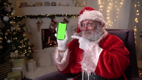 Happy Santa Claus sitting in chair near christmas tree and fireplace, showing mobile phone with green screen. Christmas spirit, holidays and celebrations concept 4k footage