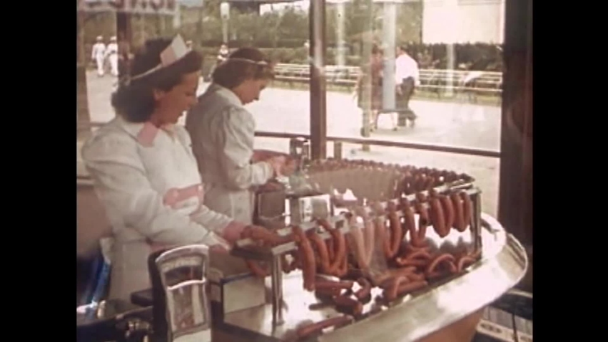CIRCA 1930s - Guests look on as women prepare hot dogs and other meats at the 1939 New York World's Fair.