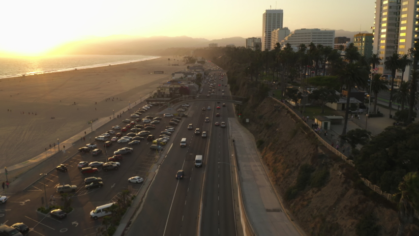 Famous Bridge overpass over Pacific Coast Highway by Santa Monica Beach in Los Angeles with light traffic in beautiful golden hour Sunset vibe, Aerial Dolly forward, Wide angle shot