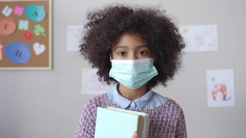 Cute small elementary reopen school pupil african american kid child girl wearing face mask looking at camera standing in classroom. Children safety for covid protection, headshot close up portrait. Royalty-Free Stock Footage #1062074263