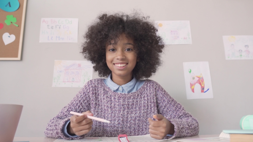 Happy african american kid child girl school student looking at web cam talking with remote teacher distance learning video conference call virtual class lesson, headshot zoom portrait, webcam view. Royalty-Free Stock Footage #1062078439