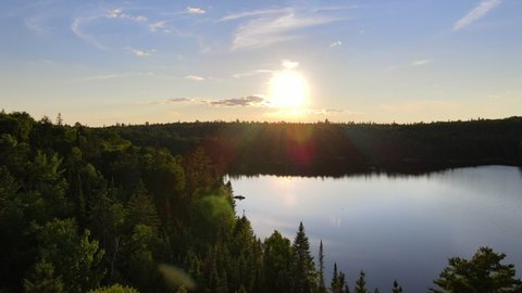 Climbing shot of a scenic sunset above a lake and forest