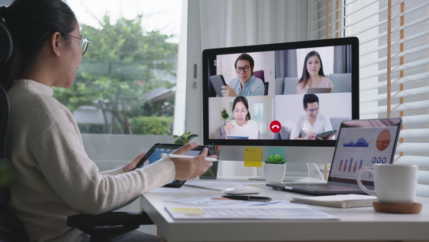 Slow zoom in business woman talking about sale report in video conference.Asian team using laptop and tablet online meeting in video call.Working from home, Working remotely and Self isolation at home | Shutterstock HD Video #1062088762