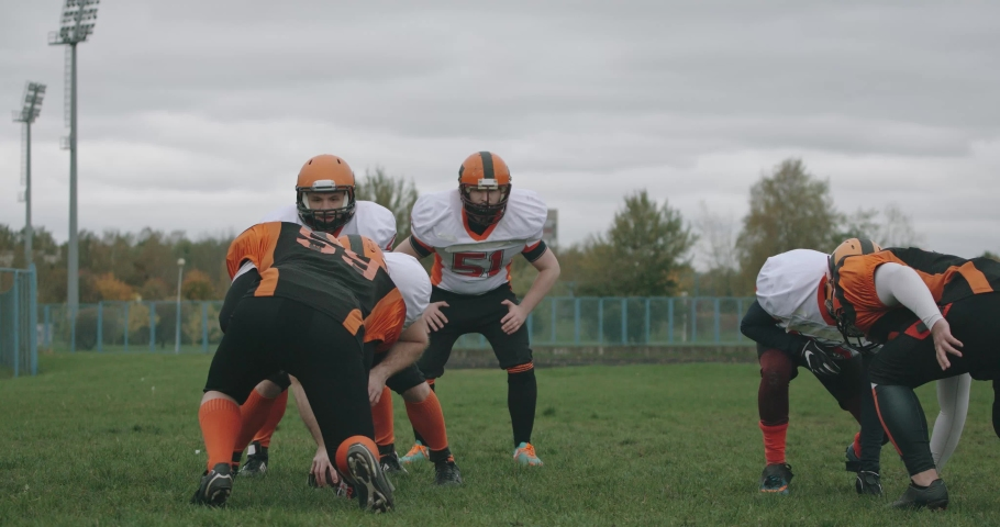American football, football players in the game, aggressive battle between players in protective gear, 4k 50fps.