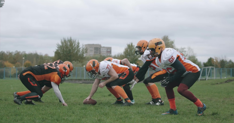 American football, football players in the game, the player catches the ball and falls to the ground, battle between players in protective gear, 4k 50fps. Royalty-Free Stock Footage #1062101416
