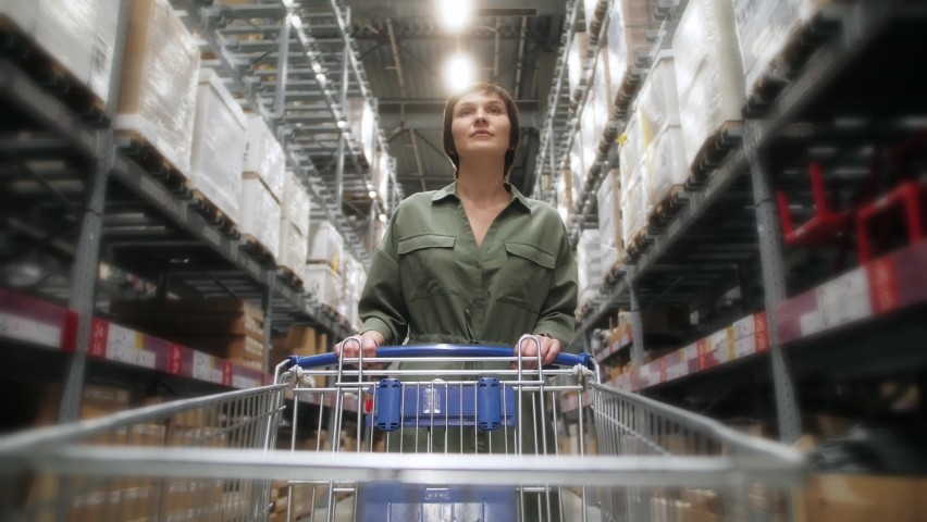 Woman with shopping trolley walking in the warehouse of large shopping centre choosing furniture and home furnishings #1062102760