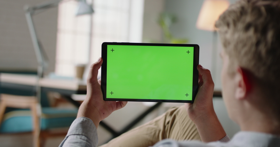 Close up shot of guy using a tablet computer with green mockup screen. Student during online lesson or work conference on self-isolation 4k footage | Shutterstock HD Video #1062108904