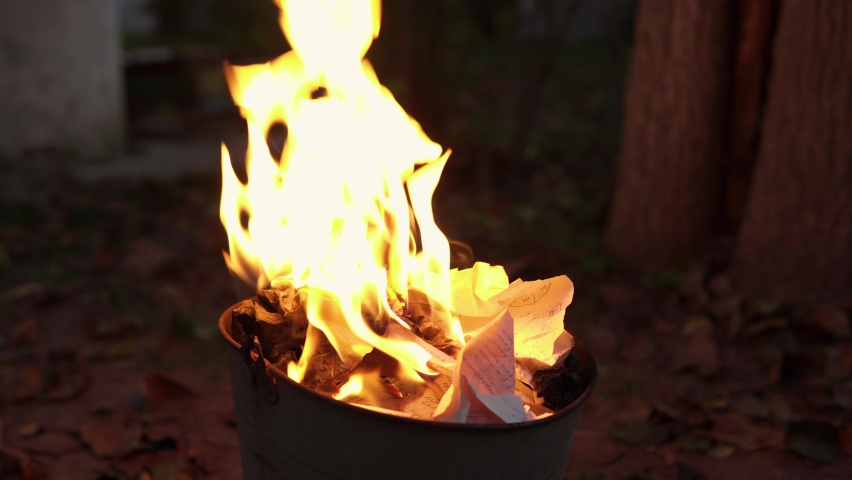 A female hand sets fire paper documents in the trash bucket. She throws other papers into the fire, all of them burning out.