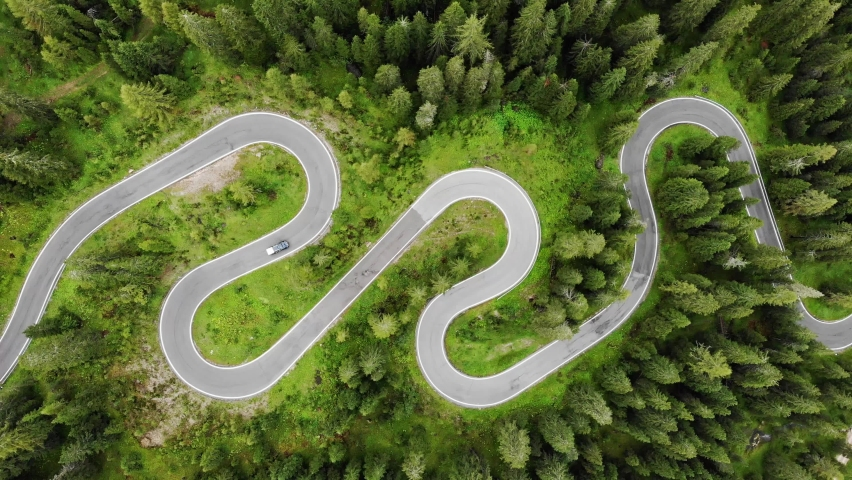 Aerial top down drone shot above the winding mountain road between the trees near Passo Giau in Dolomites, Italy. Overcast late summer weather. Car driving through the curve 4K. Flying straight up | Shutterstock HD Video #1062111562