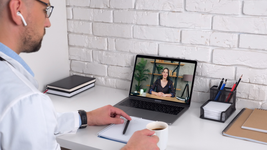 Woman in laptop screen communicates talk speak medical worker remote webcam. Distance man doctor in hospital office listens patient client online by conference video call computer, drink coffee tea | Shutterstock HD Video #1062114055