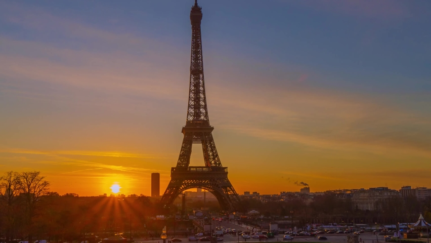 4K timelapse of Paris at sunrise with the Eiffel Tower at the Trocadero gardens and the traffic,the most famous landmark in Paris,France.Golden hour in an autumn winter sunny day in