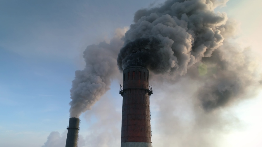 Very dirty dark smoke comes out in horrific clouds from old chimney of factory plant, polluting environment. Toxic production company. Industrial enterprise. Winter. Aerial gain attitude close up