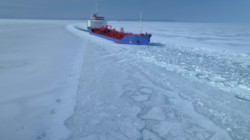 Drone sideways close steel grand icebreaker cinematic iceboat floats breaks snowy ice in frozen endless sea, made an expedition to Arctic North. Contrast red blue deck. Horizon open space. Travel  | Shutterstock HD Video #1062115156