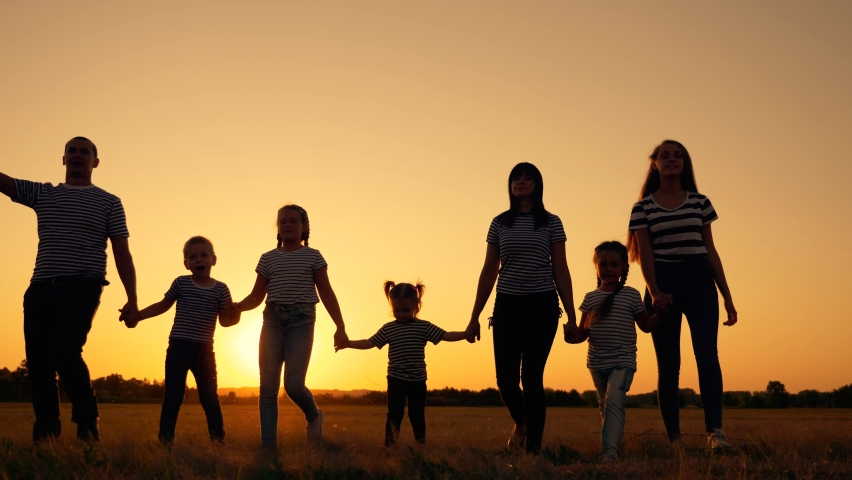 Happy big family in the Park at sunset. People on a walk have fun. Mom dad son and daughters walk together in the field. People holding hands, teamwork. Family trip on foot.