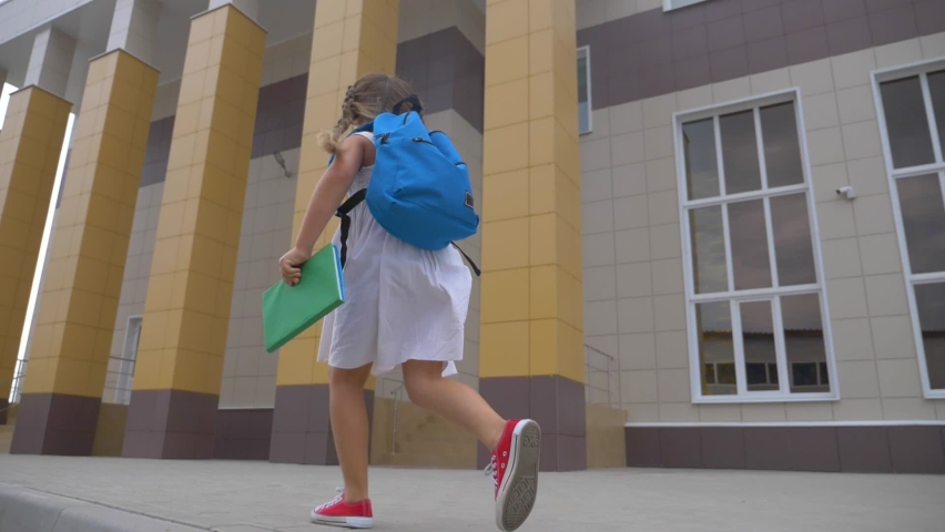 A small schoolgirl with a backpack and a book runs through the Park to school. A girl with a school backpack hurries to class. Educated children.   Shutterstock HD Video #1062120958