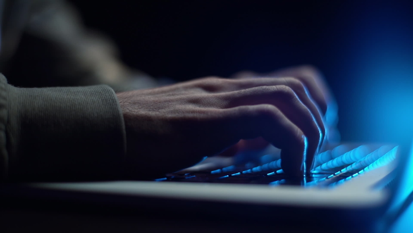Extreme close-up hands of unrecognizable hacker programmer working typing on keyboard laptop computer at dark room. Freelancer using laptop working from home, soft blue color. Shooing in slow motion. Royalty-Free Stock Footage #1062142567
