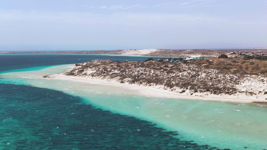 Aerial Reveal of blue waters in Coral Bay section of Ningaloo Reef seen from above. Western Australia Tourism. A sanctuary for whale sharks, turtles and manta rays. Royalty-Free Stock Footage #1062146473