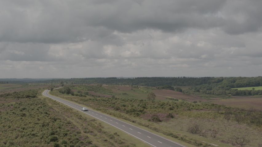 Aerial Drone Shot of English UK Countryside in The New Forest with Road and Cars in moody stormy weather