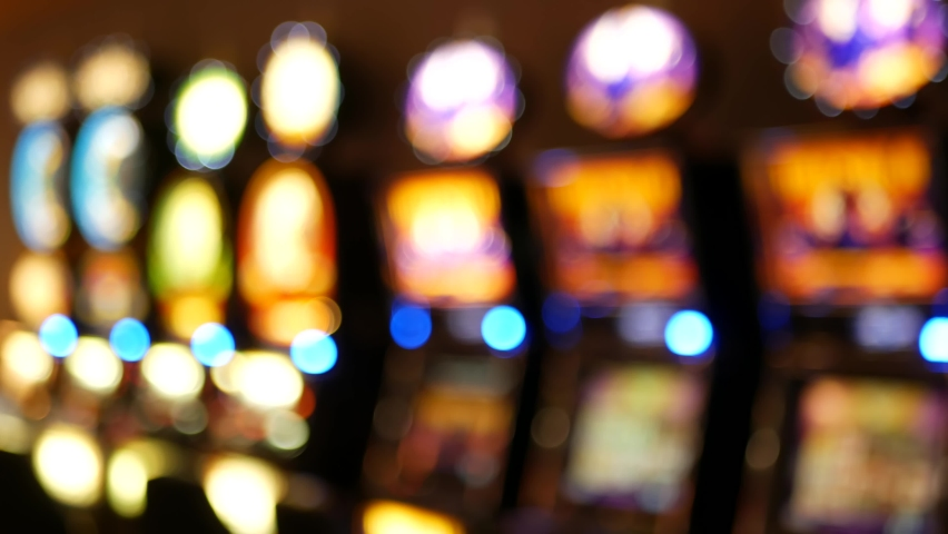 Defocused slot machines glow in casino on fabulous Las Vegas Strip, USA. Blurred gambling jackpot slots in hotel near Fremont street. Illuminated neon fruit machine for risk money playing and betting. | Shutterstock HD Video #1062164485
