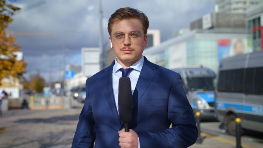 Handsome Young Man Journalist In Suit And Tie Presenting Breaking News TV About March Protest Coronavirus Pandemic On Street Outdoors Cars On Signals Police In Background Pandemic City Slow Mo
