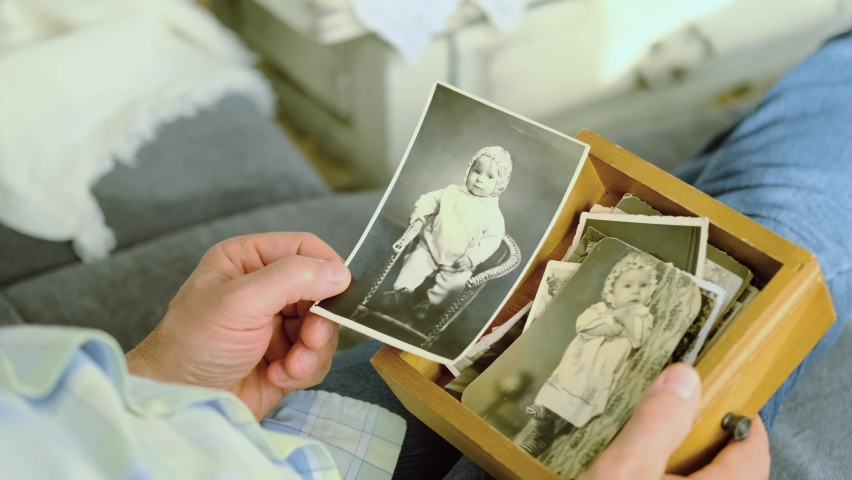 an elderly man looks through his old photographs of 1960-1970, the concept of nostalgia and memories of youth, childhood, remembering his life, relatives, family connection of generations Royalty-Free Stock Footage #1062169372