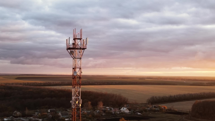 Telecommunication tower of 4G and 5G cellular or Base Transceiver Station. Wireless Communication Antenna Transmitter. Aerial view of antennas against sunset sky. Royalty-Free Stock Footage #1062171994