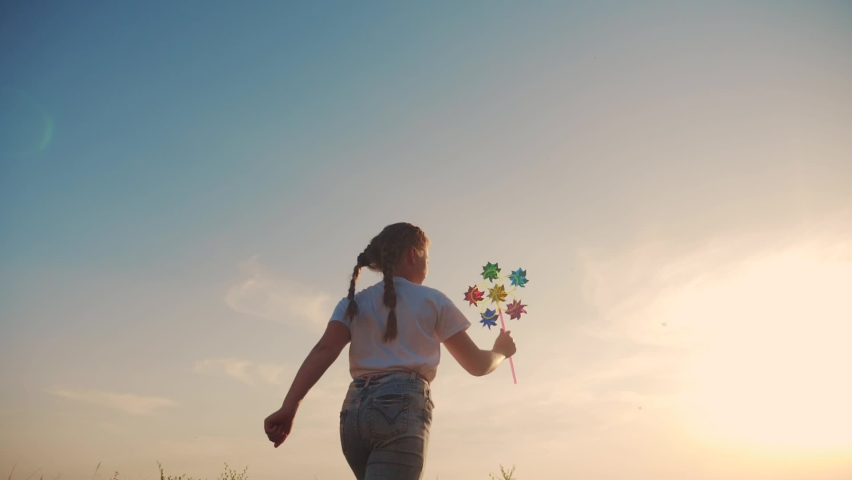 Dream concept. little girl kid run near the field at sunset silhouette with holds in hands toy turntable pinwheel. lifestyle happy family kids concept. happy daughter runs along rural road to meet the