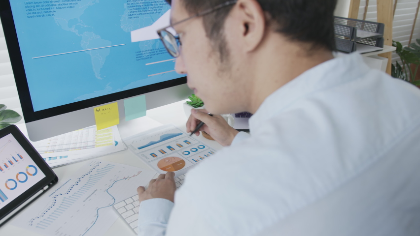 Over head shoulder back view of young attractive asian thai man busy work multiple screen computer or smart tablet on table desk at home in freelance data analyst, data science scientist for business. Royalty-Free Stock Footage #1062183433