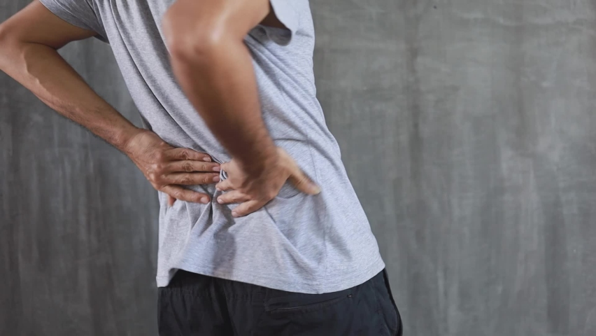 a young man suffering from back pain Royalty-Free Stock Footage #1062184741