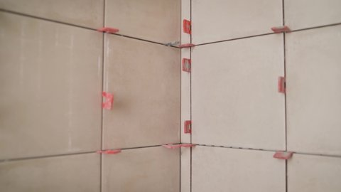 Repair of tiles in the bathroom. Close up of tiles fixing wall tiles with spacers at home, renovation work