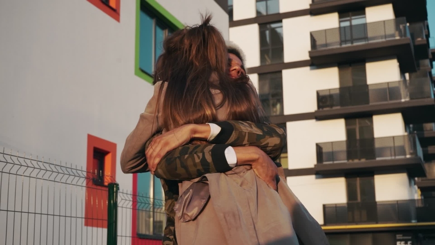 Emotional afro american man hugging and kissing his charming young girlfriend during sunny day on street. Young couple meeting on fresh air. Concept of relationship.   Shutterstock HD Video #1062196186