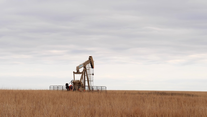 OSAGE CO., OKLAHOMA - 2 MAR 2020: Oil Well Pump Jack pumping crude oil for fossil fuel energy. American Petroleum Oil and Gas Industry equipment extracting oil from a field on a prairie. Slow zoom in.
