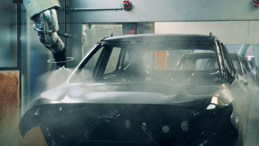 Robotic arms spray painting a vehicle body at a car manufacturing factory Royalty-Free Stock Footage #1062202435