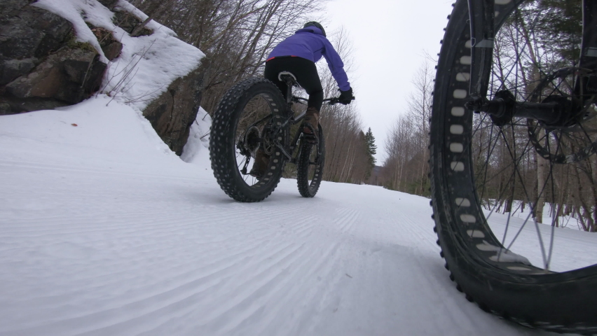 Biking in winter on fat bike. Woman fat biker riding bicycle in the snow in winter. Close up action shot of fat tire bike wheels in the snow. People living active winter sports lifestyle | Shutterstock HD Video #1062208081