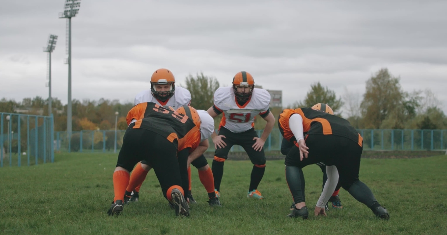 American football, football team in the game, training aggressive opposition during the game, the fight between players and successful passing the ball, 4k 50fps. Royalty-Free Stock Footage #1062225796