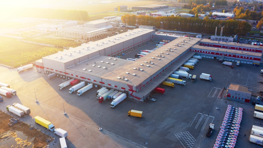 Logistics park with a warehouse - loading hub. Semi-trailers trucks standing at the ramps for loading/unloading goods at sunset. Aerial hyper lapse (motion time lapse). Royalty-Free Stock Footage #1062225952